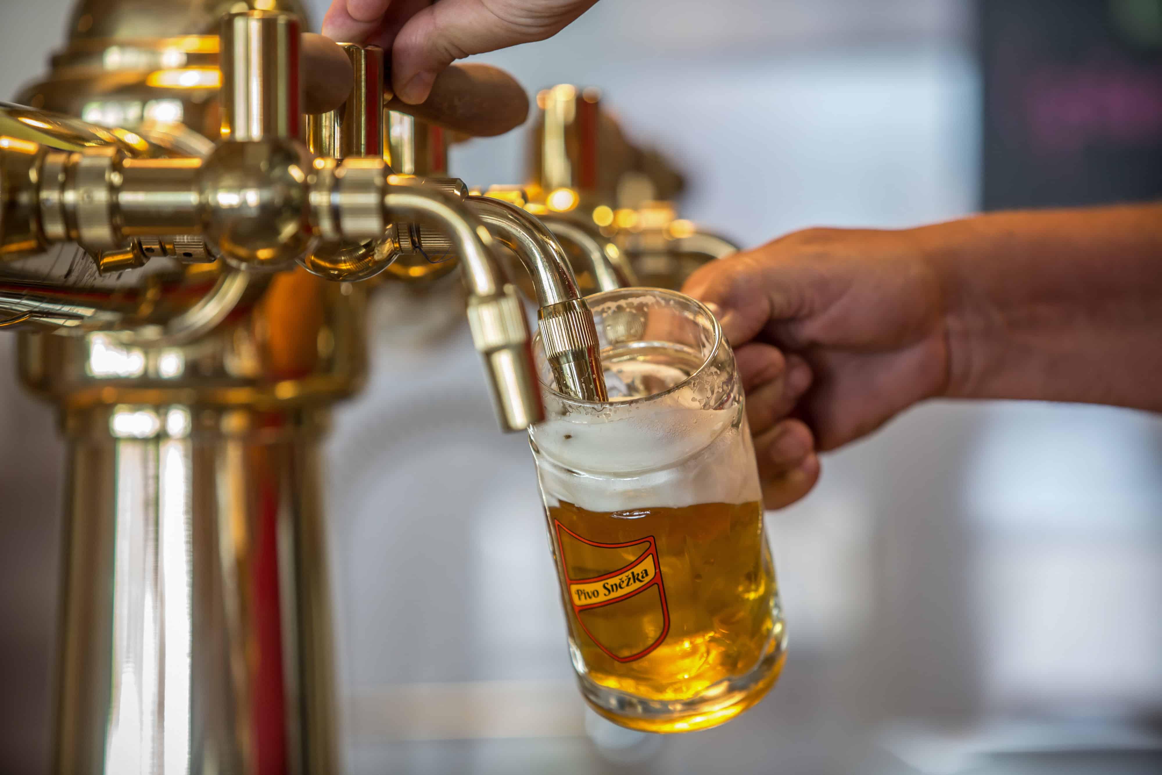 Een pint bier wordt getapt uit een gouden tapkraan.