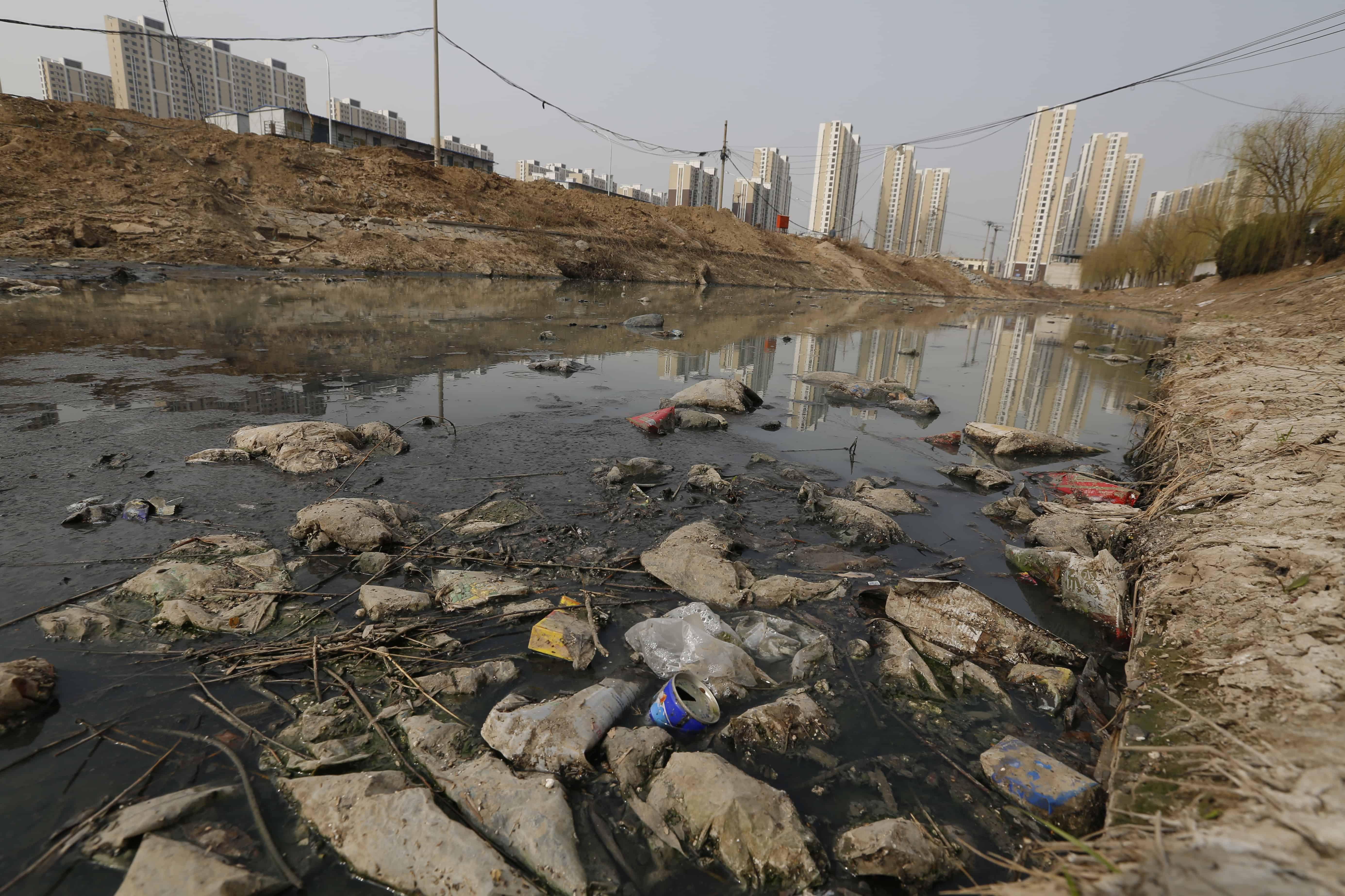Une rivière polluée regorgeant de déchets plastiques en Chine avec des gratte-ciels à l'arrière-plan.