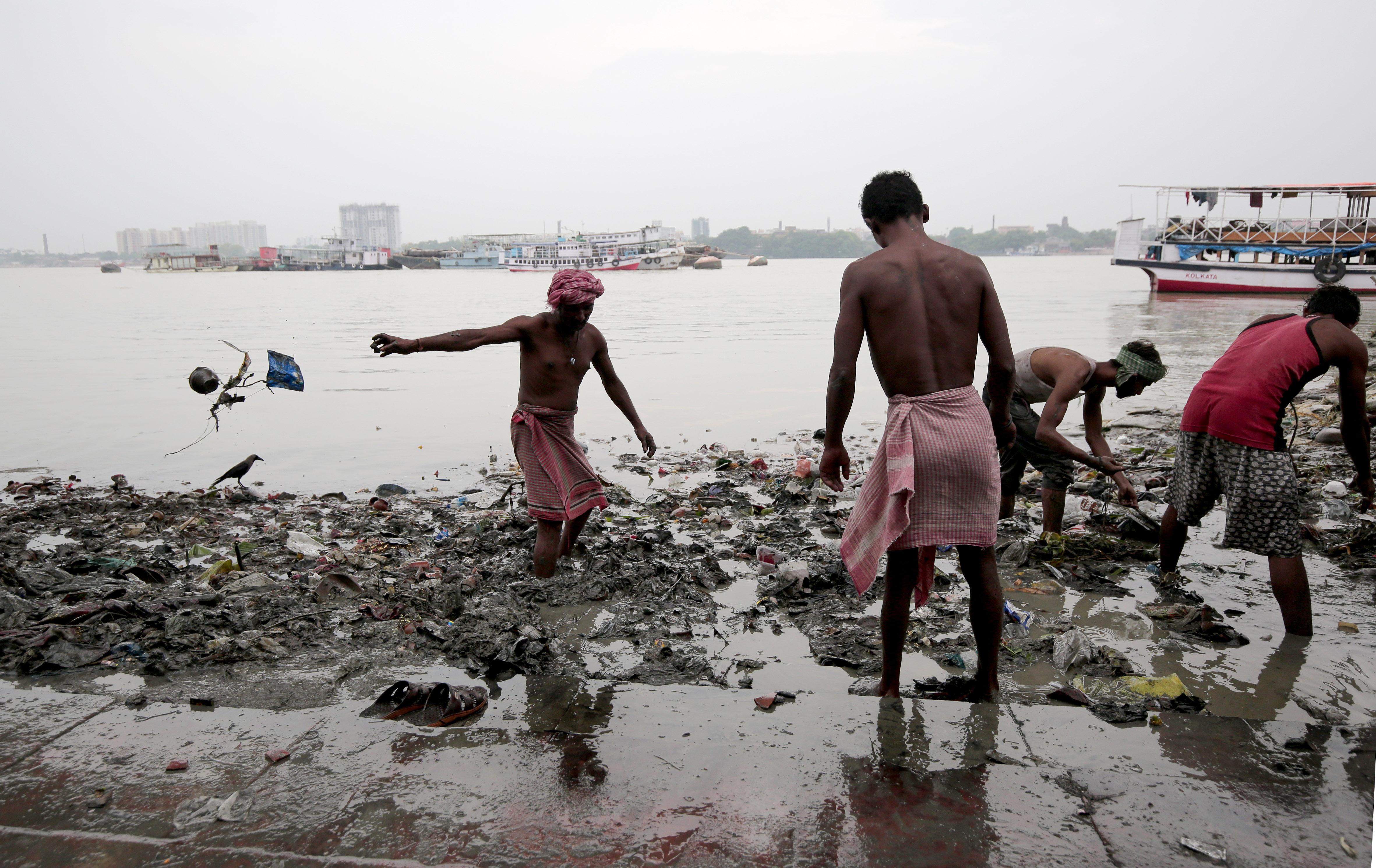 Mensen lopen door met plastic bezaaid water in India, een land waar de watercrisis ernstige gevolgen kent.