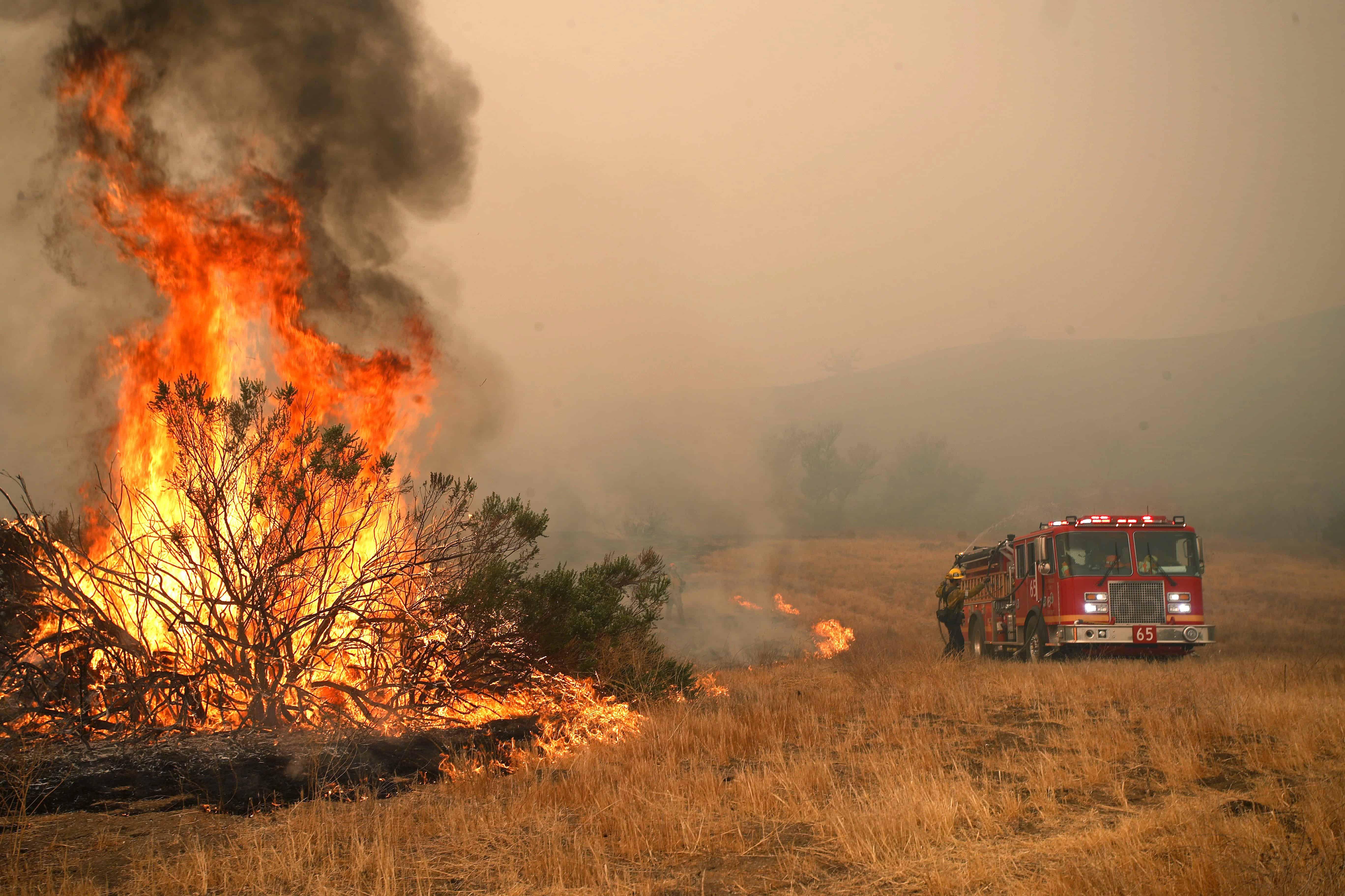 Een brandweerwagen komt aangereden terwijl naast de weg een grote bosbrand woedt.