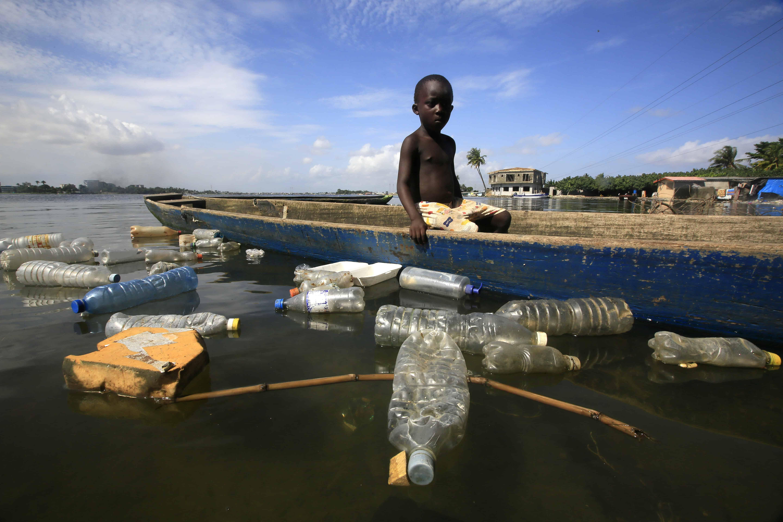 Een zwarte jongen wordt omringd door plastic in het water. Ook dit maakt deel uit van de globale watercrisis.