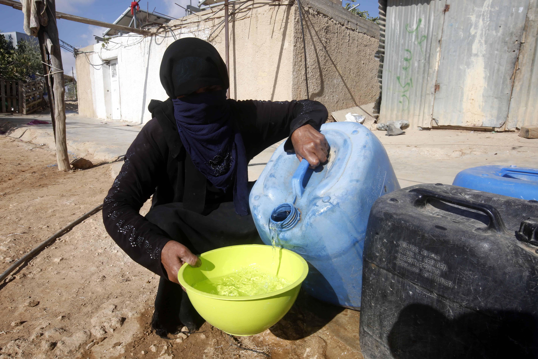 Een vrouw met boerka giet water uit een bidon in een gele kom om te koken, terwijl ze gehurkt in het zand zit. Grote delen van de wereld bevinden zich in een watercrisis.