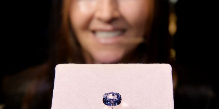 "Suzette Gomes, CEO of Cora International, poses with the 12-carat ""Blue Moon Diamond"" which is on display at the Natural History Museum in Los Angeles on September 12, 2014. The 'Fancy Vivid Blue Diamond' which are extremely rare was discovered in South Africa. AFP PHOTO/Mark RALSTON / AFP PHOTO / MARK RALSTON"
