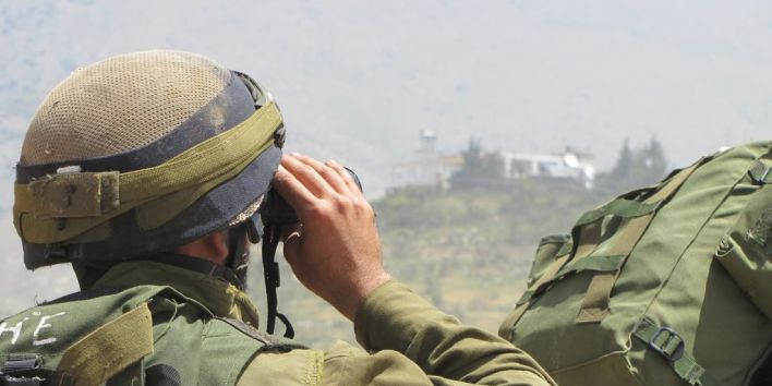 Soldier checking border with binoculars