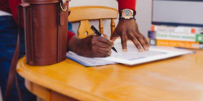man write list work pen paper