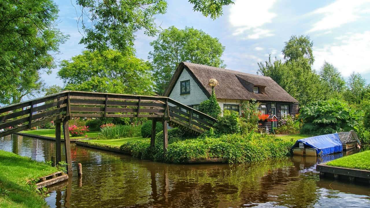Een houten voetgangersbrug over het water leidt naar een huis in het Nederlandse Giethoorn.