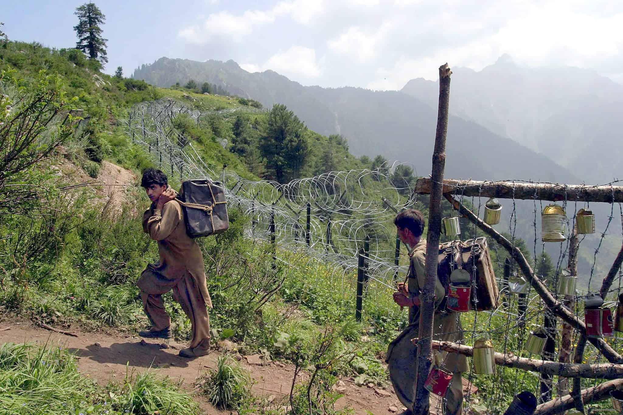 Twee mannen lopen met zakken vol kerosine op de rug langs een controlepost in India.