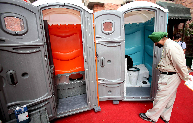 Een Indiër kijkt binnen in een toiletbox op een beurs.