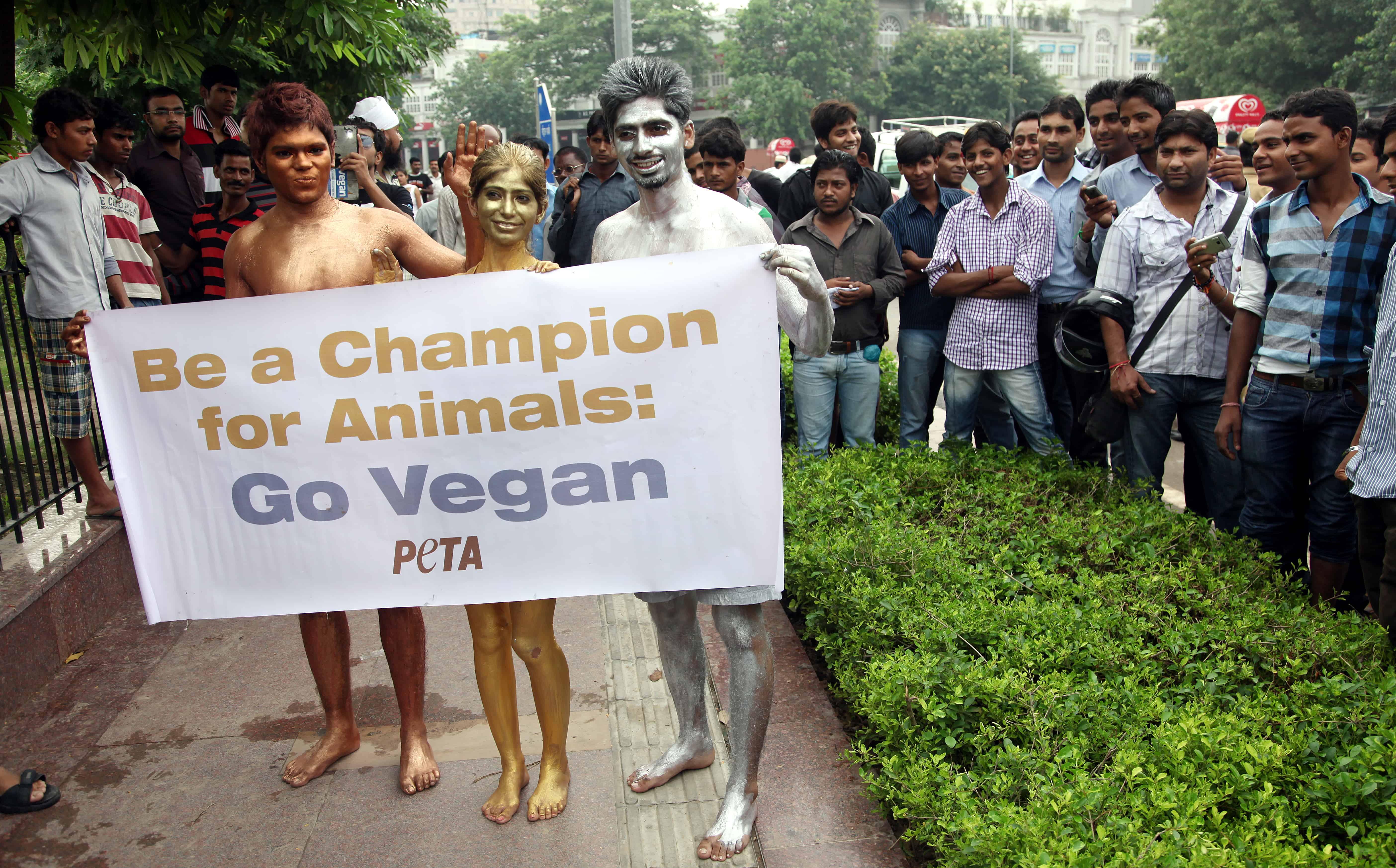 Naakte in goud, zilver en brons geverfde actievoerders houden een vaandel met een boodschap voor vegetariërs vast.