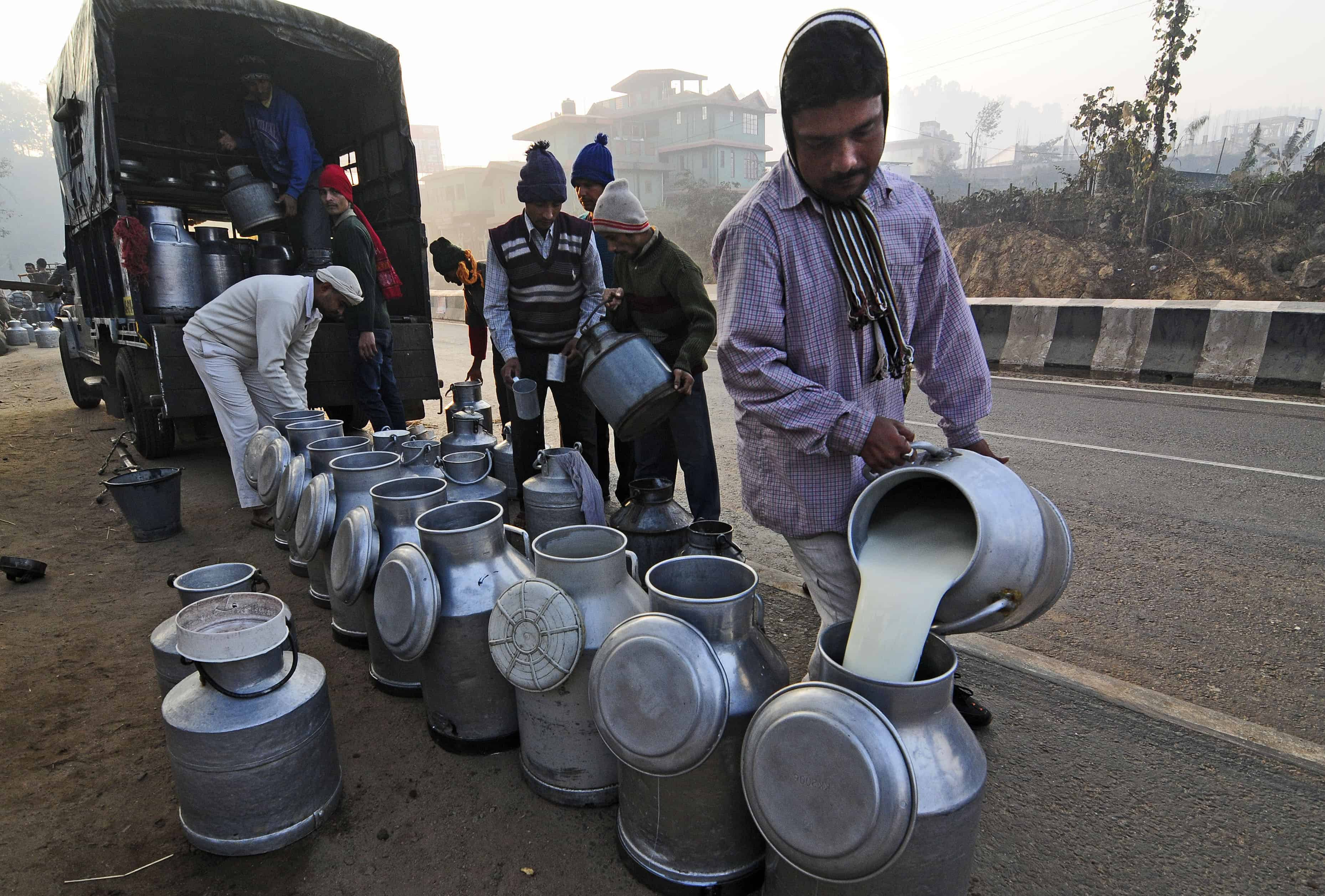 Een man giet melk in een kan, met daarachter een rij kannen en een wagen.