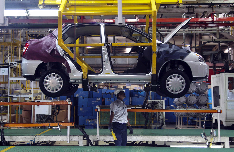 Een man staat onder het geraamte van een auto in een fabriek in India.