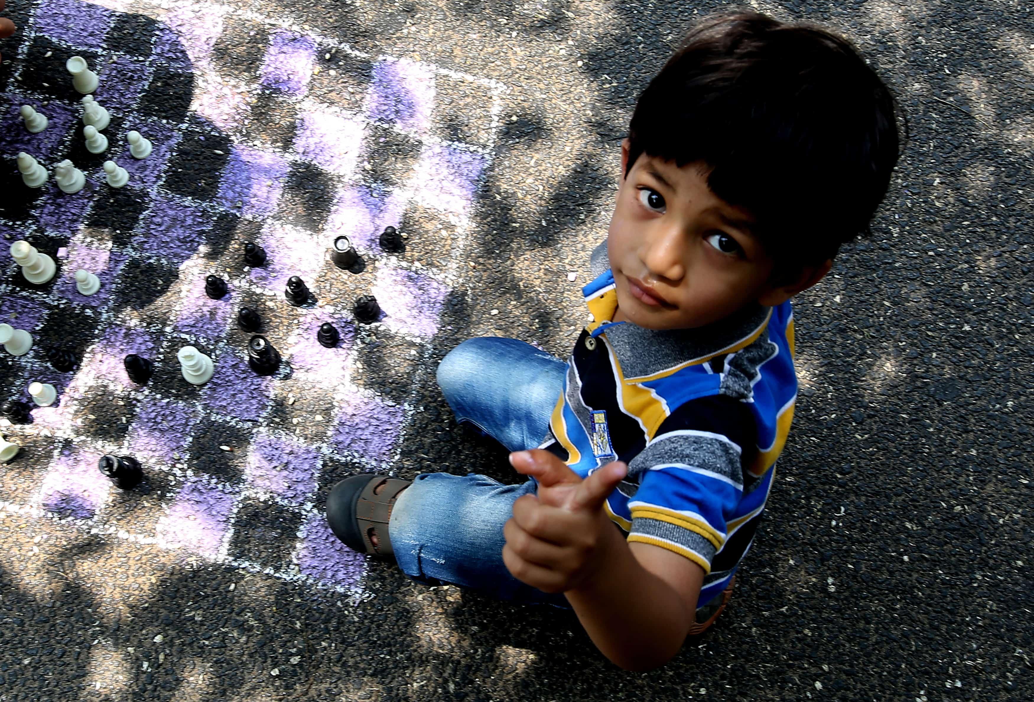 Een Indisch kinds wijst met z'n vinger omhoog tijdens een spelletje schaken. Het schaakbord is met krijt op het asfalt getekend.