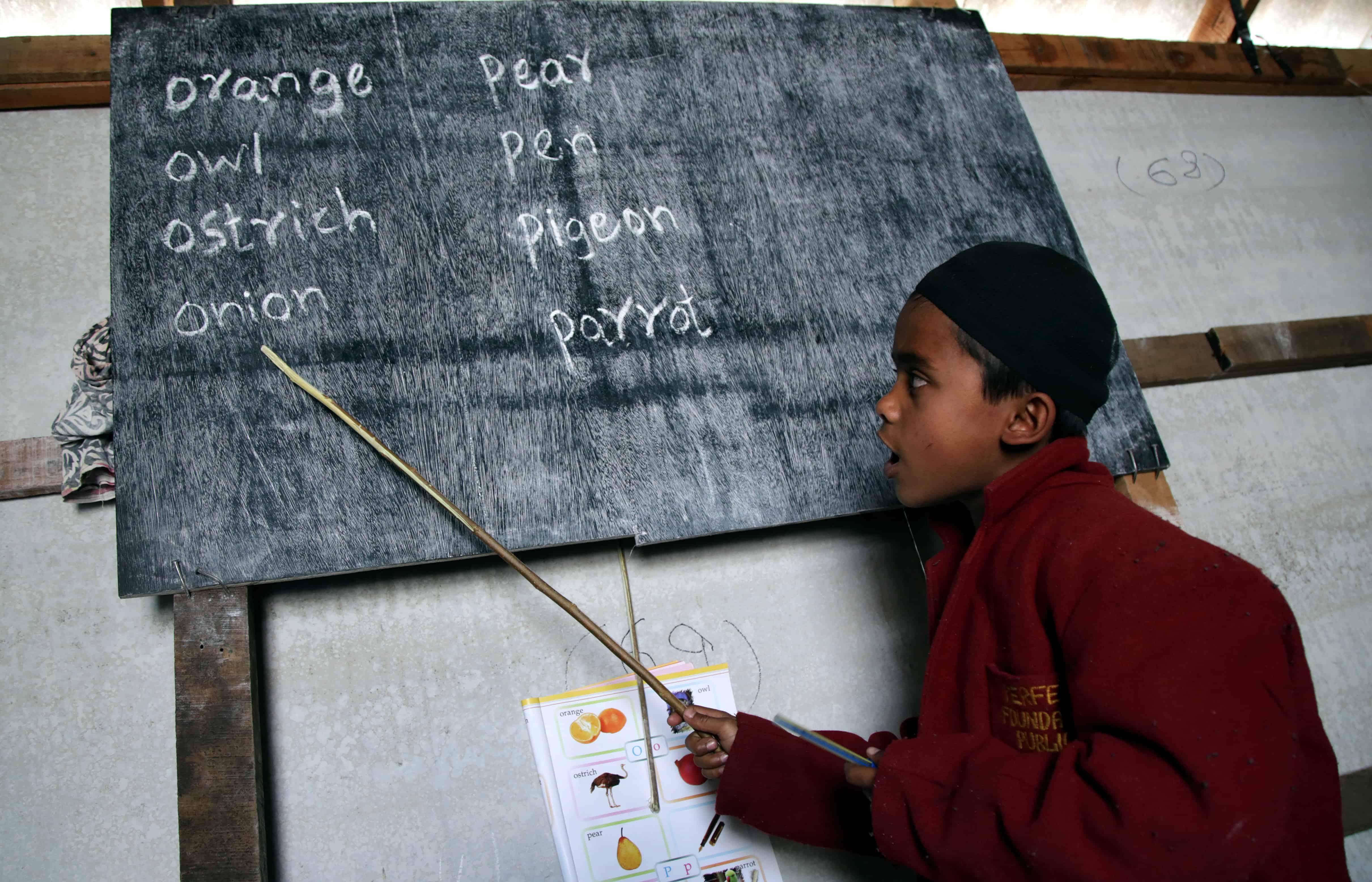 Een kind wijst met een stok naar een bord waar Engelstalige woorden op staan.