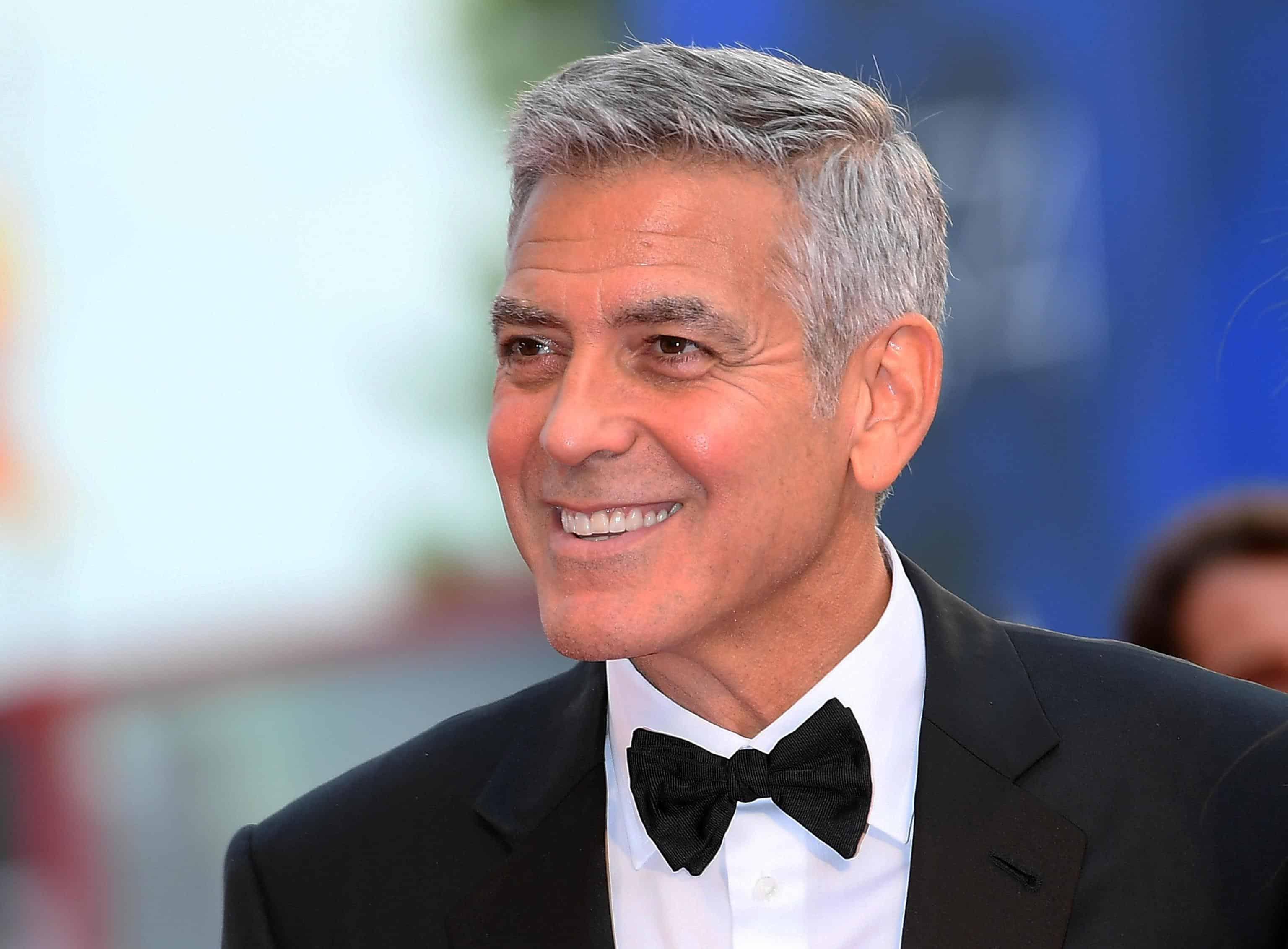 George Clooney in kostuum met strikje lacht.
