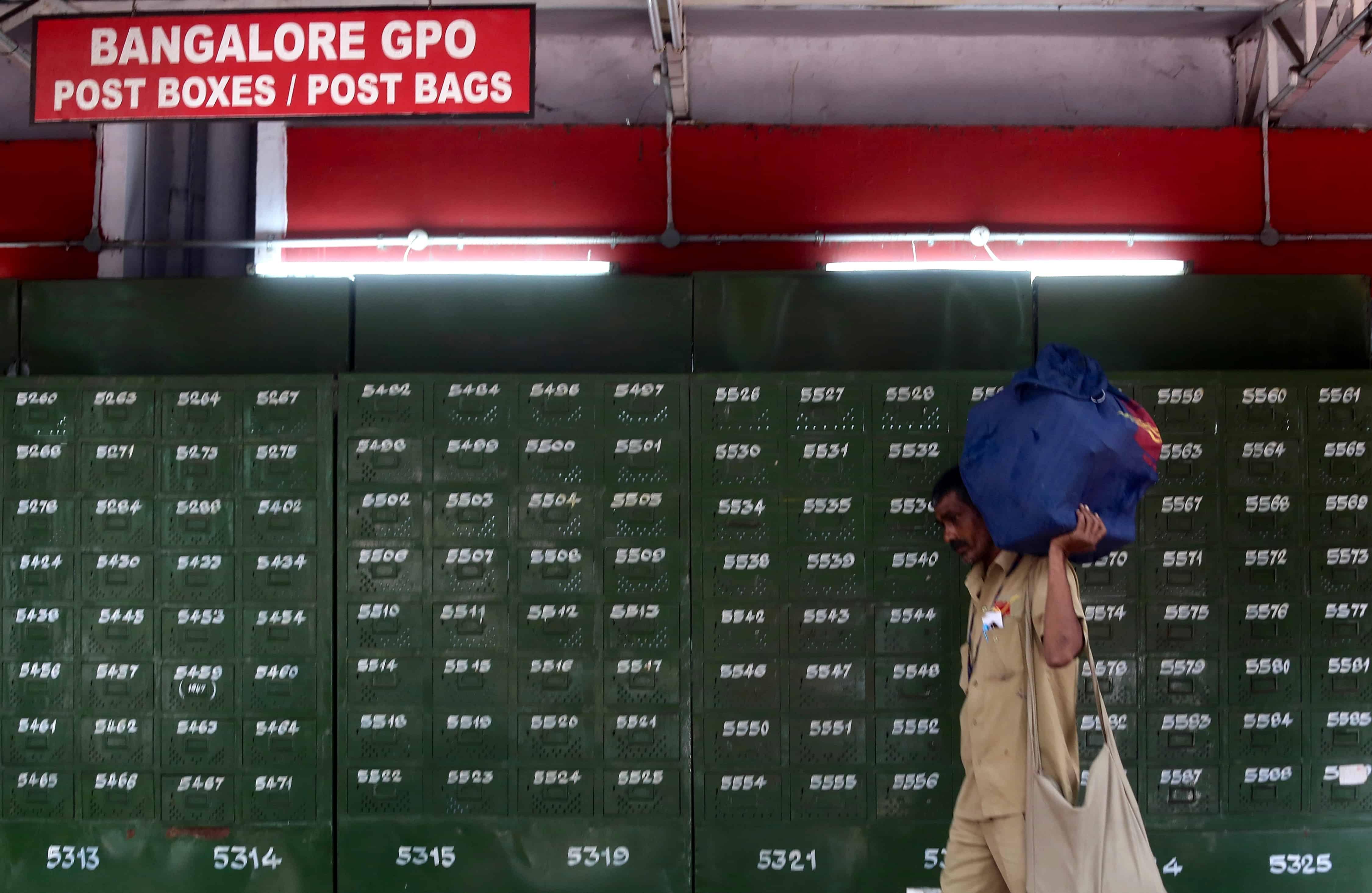 Een man loopt met een zak langs brievenbussen van een postkantoor in India.