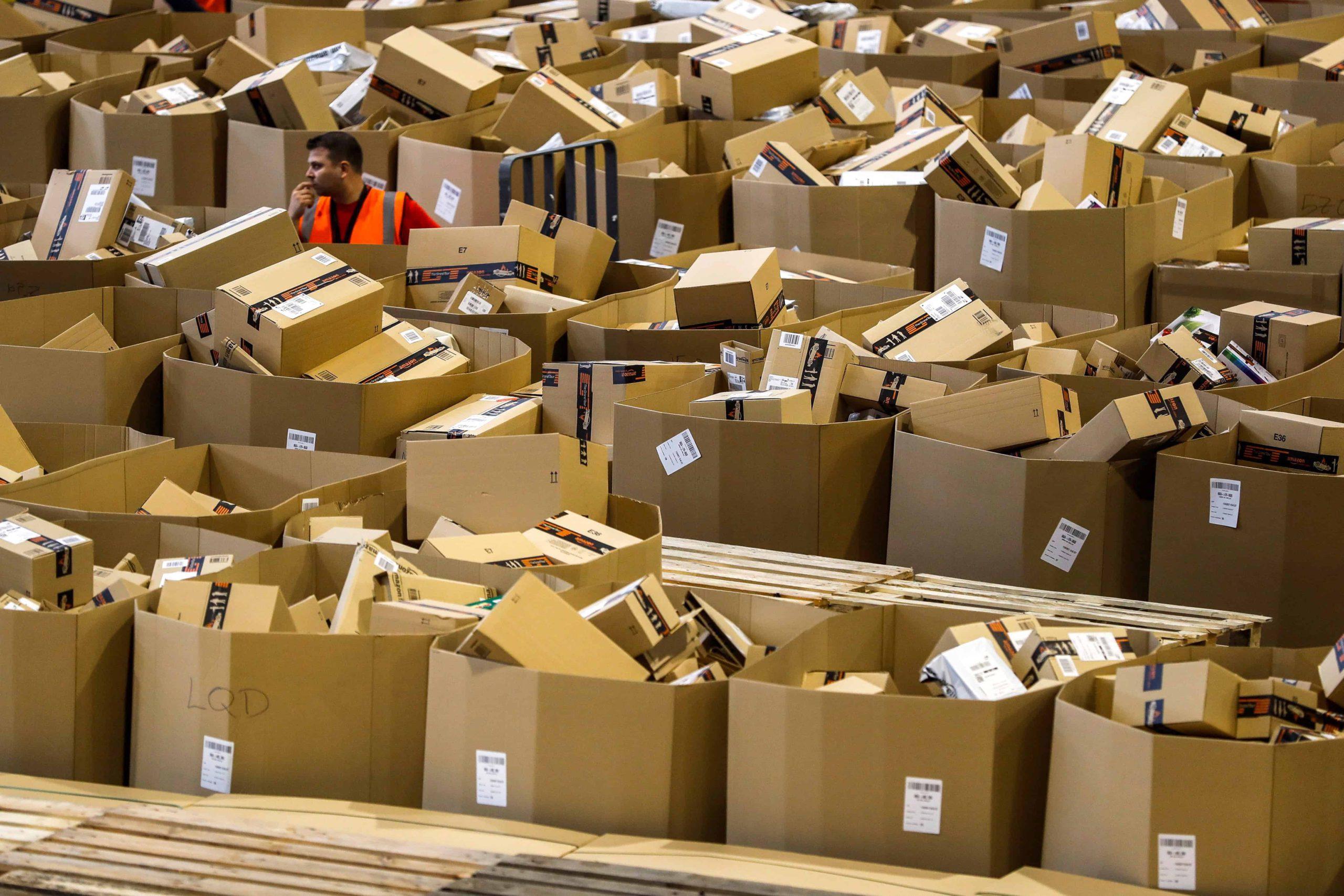 Un employé s'affaire au milieu de cartons dans un centre de traitement de commandes d'Amazon