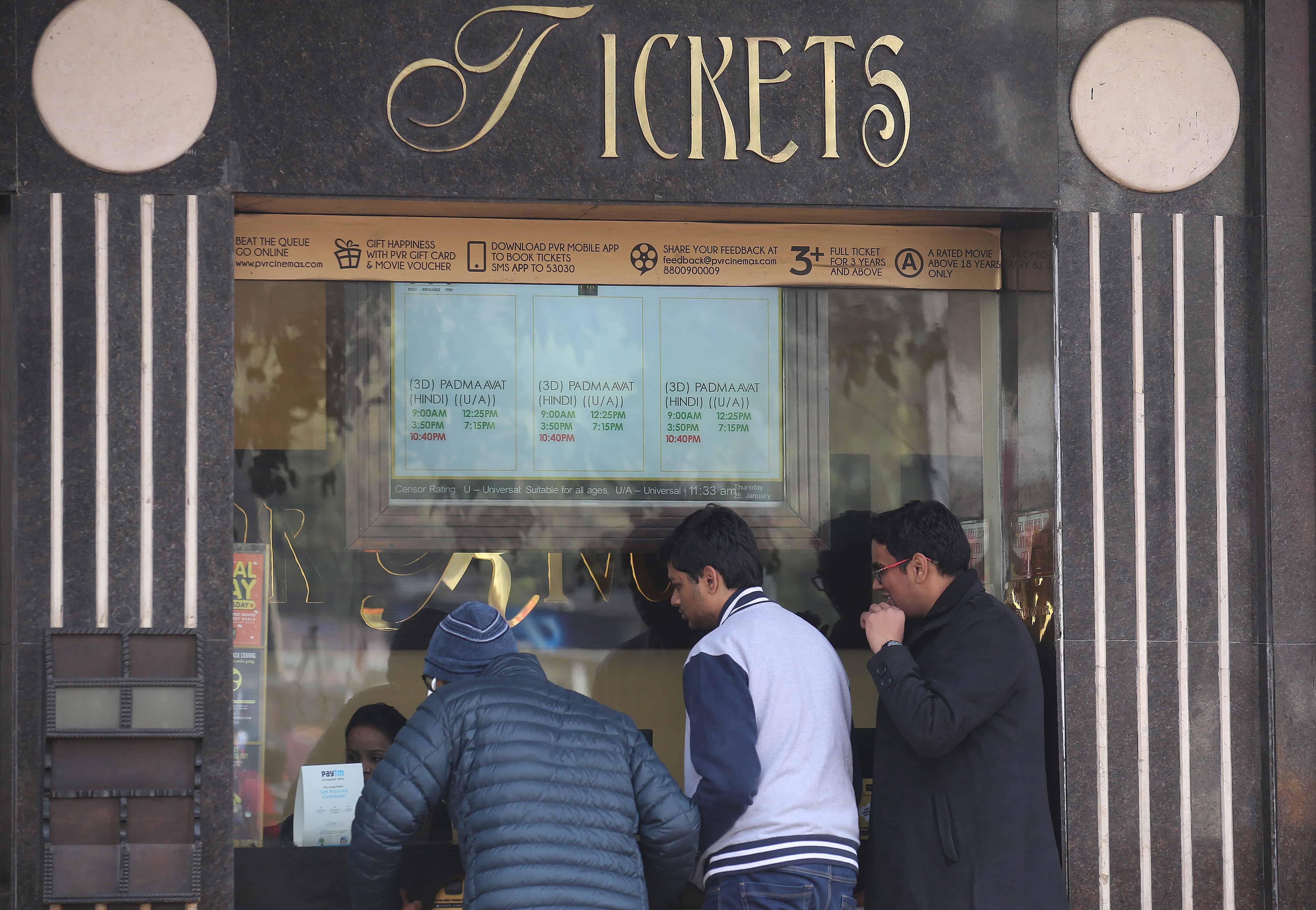 Drie mensen staan aan een kraampje voor bioscooptickets in India.