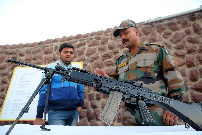 Een Indische soldaat legt een man uit hoe een machinegeweer werkt.