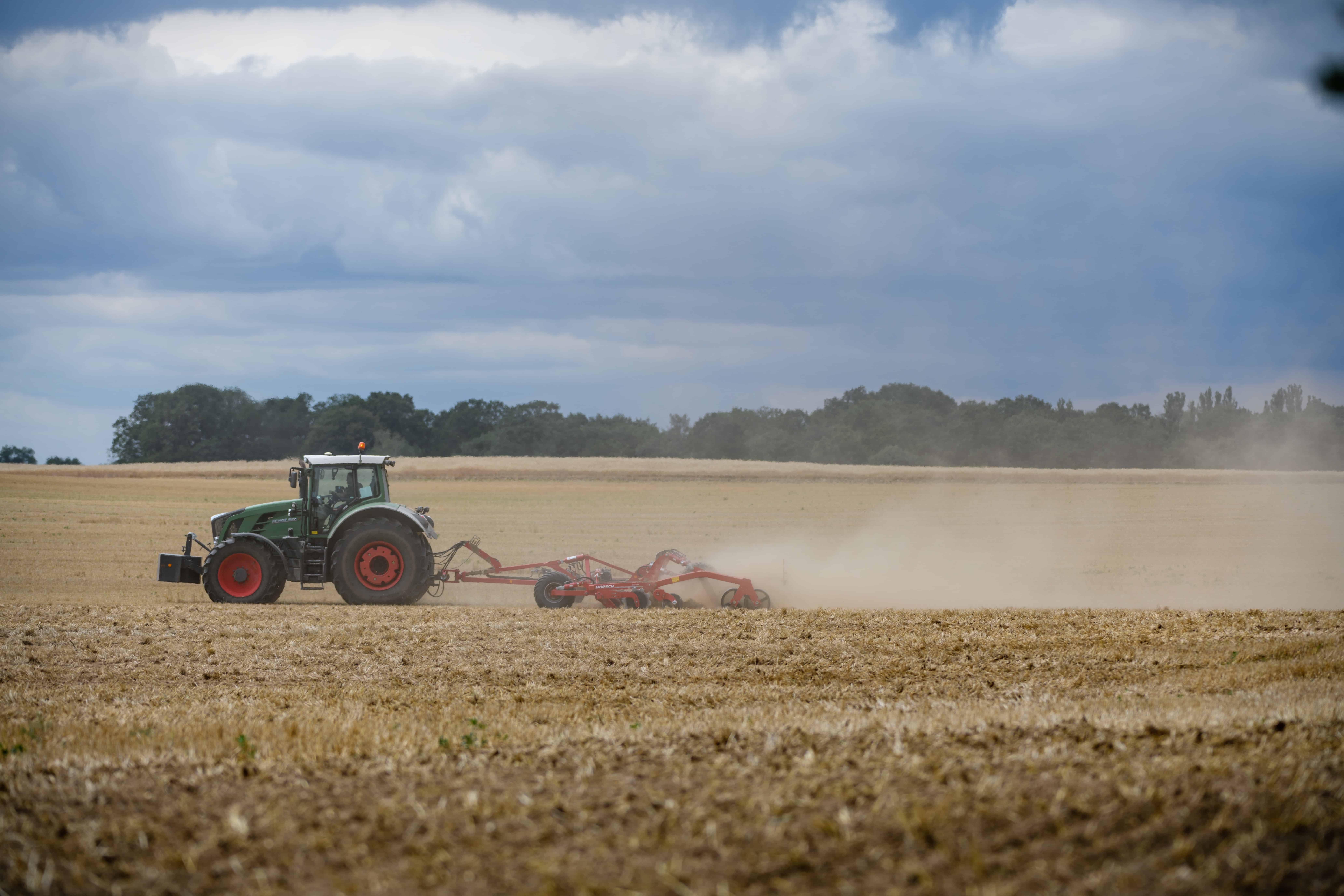 Een tractor rijdt over een veld. Ook de landbouw wordt zwaar getroffen door waterschaarste.