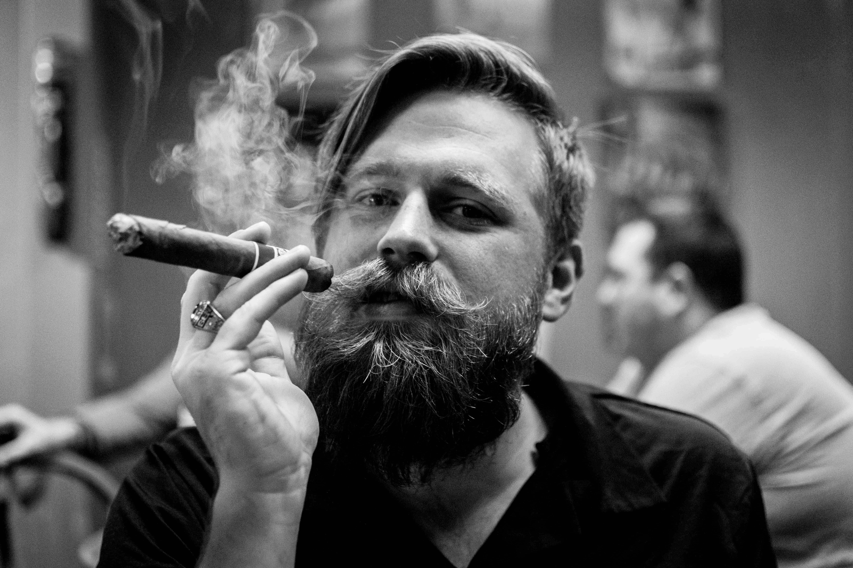 Un homme barbu tient un cigare.