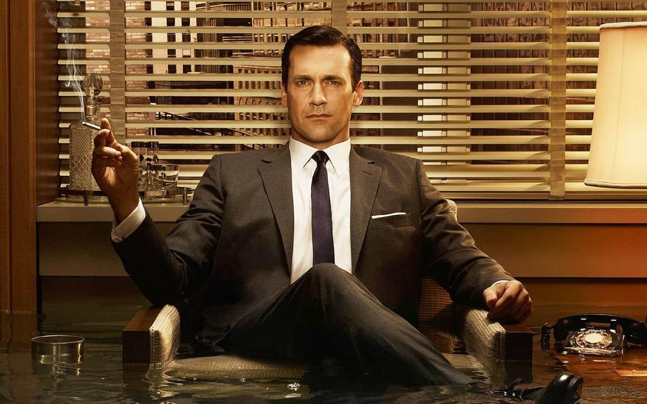 Don Draper houdt een sigaret vast in 'Mad Men'. Mooie mensen hebben meer invloed.