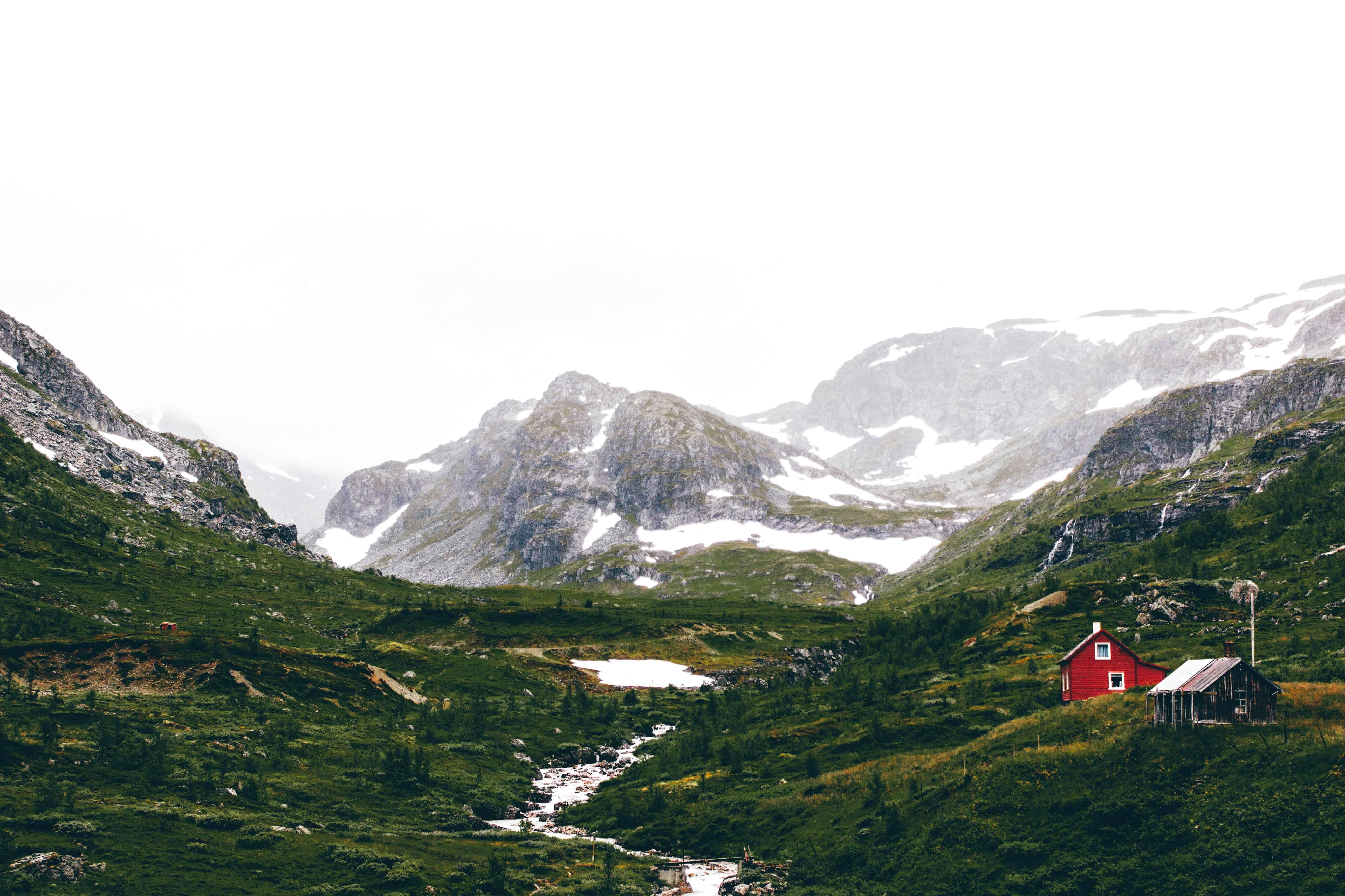 Een rood huisje met op de achtergrond een gletsjer in het Noorse Flam.