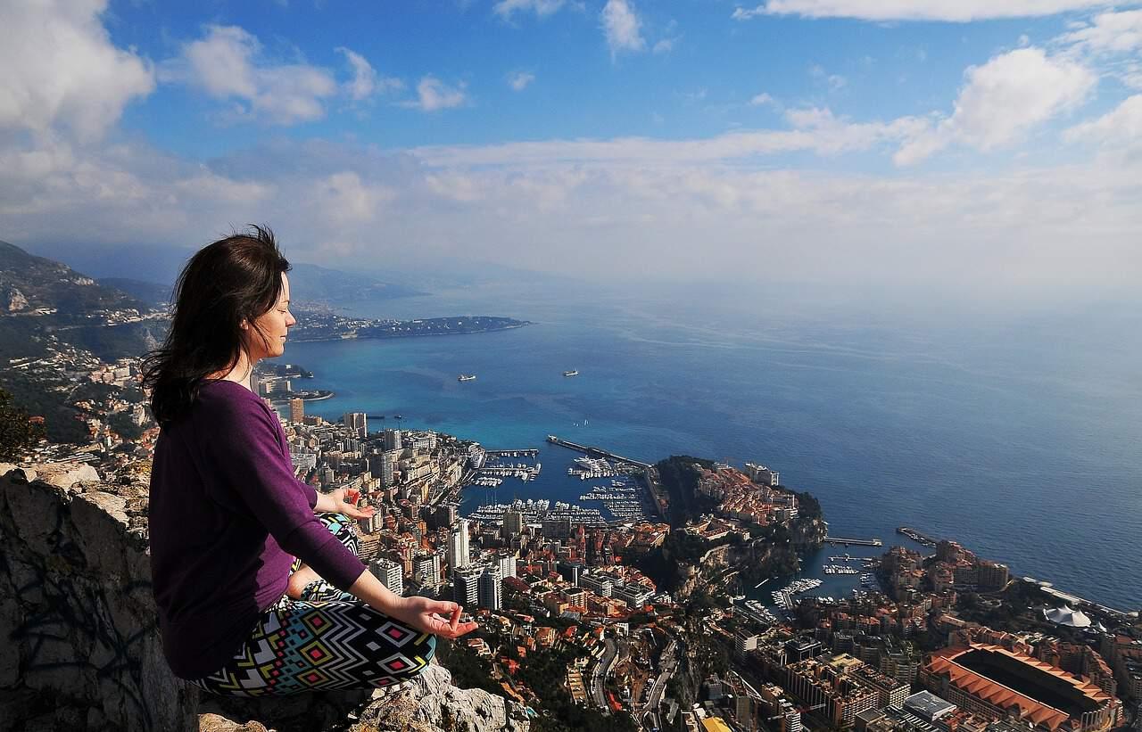 Une femme médite avec vue sur Monaco.
