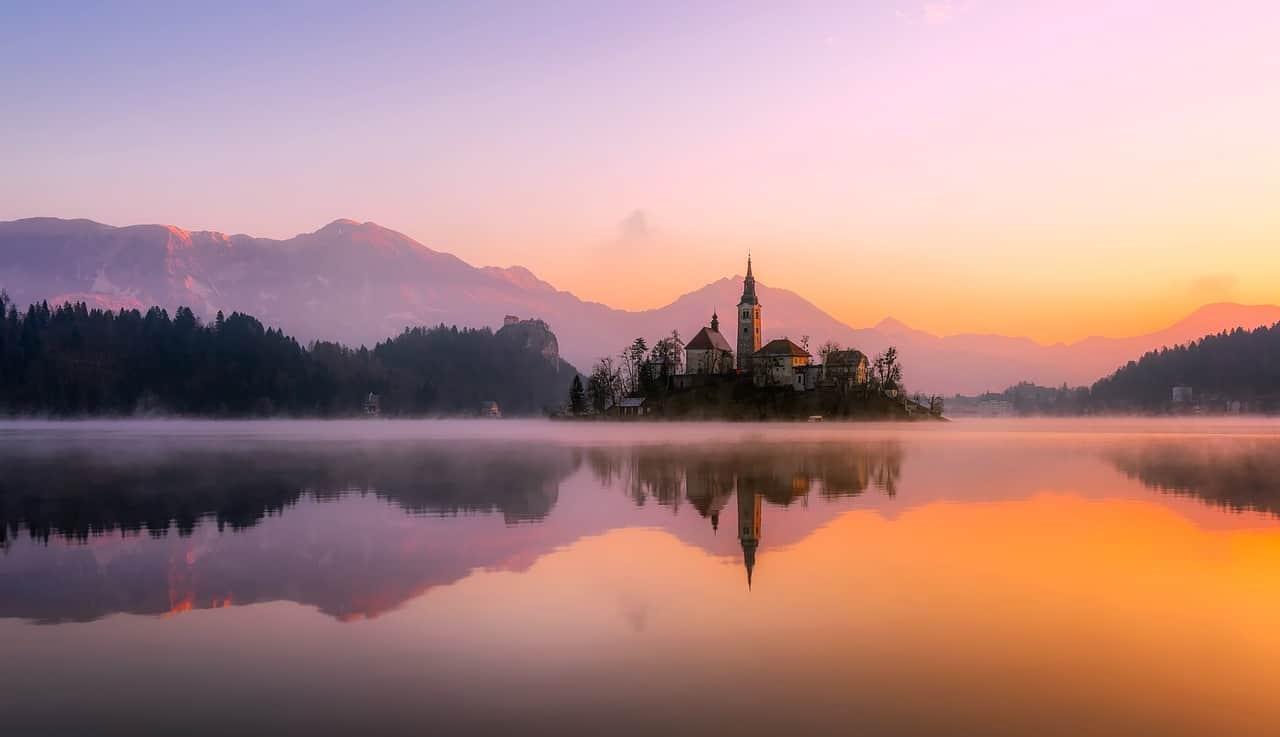 De Sloveense stad Bled in de avondschemering aan het water.