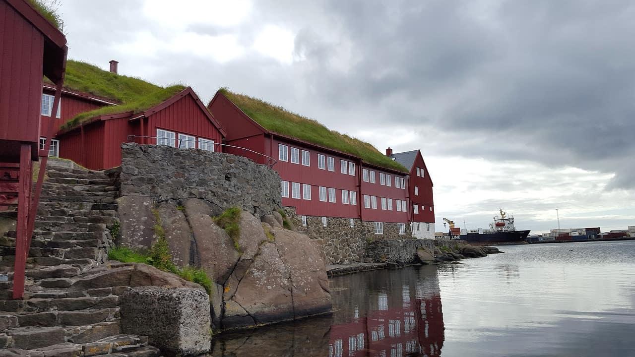 Rode huizen en met gras bedekte daken langs de oever in Torshavn op de Faeröer.