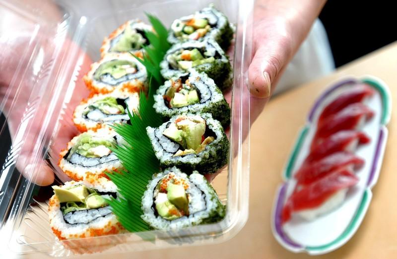 Le chef d'un restaurant de plats à emporter commandés en ligne montre une boîte de sushis prête à être livrée