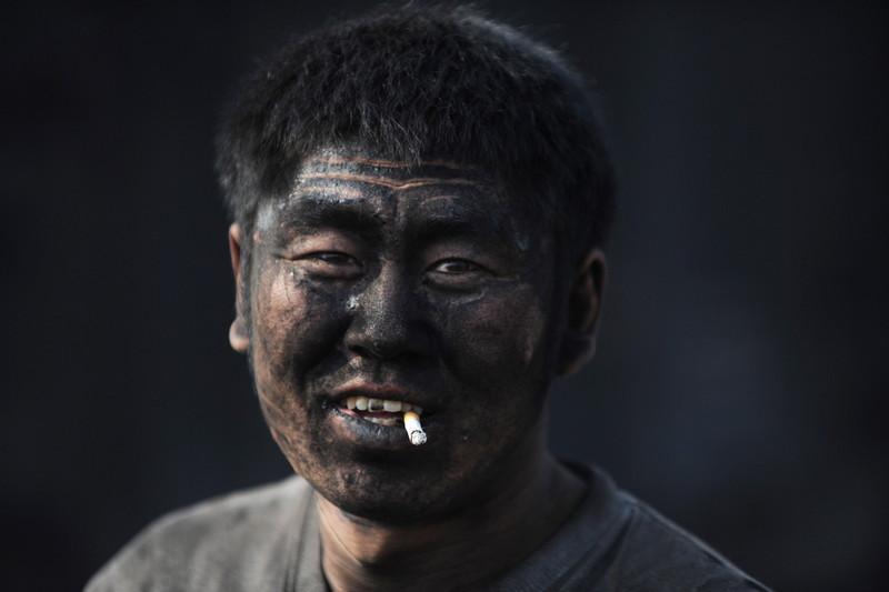 Un Chinois travaillant dans une centrale à charbon en Chine fume une cigarette