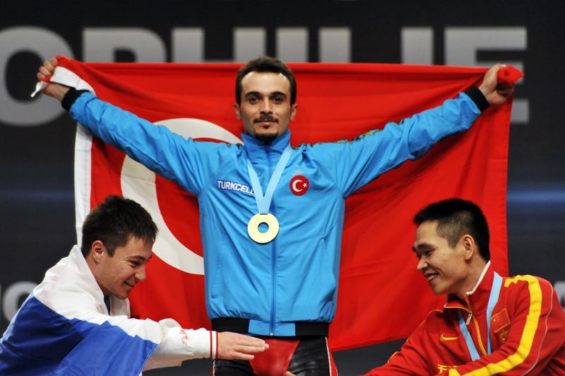 Le champion du monde d'haltérophilie, Biney Mete, déploie le drapeau de la Turquie sur le podium. La Turquie est aussi championne du monde de l'adoption des monnaies virtuelles