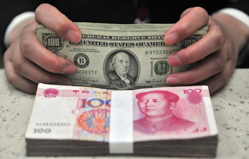 Un employé d'une banque en Chine convertit des dollars en yuan
