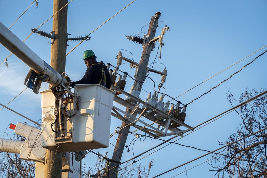 Un technicien répare une ligne électrique après le passage de l'ouragan Dorian, une catastrophe qui a affecté les Bahamas
